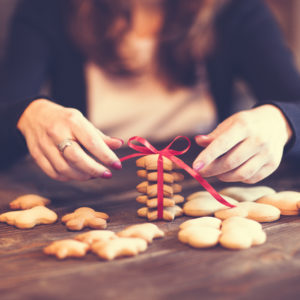 Close up image of a woman baking and decorating cookies